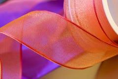 弓关闭卷起橙红丝带 免版税库存照片