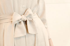 弓在米黄妇女的传送带领带细节穿戴成套装备样式 塑造时髦 库存图片