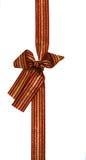 弓礼品金子查出的褐红的丝带 库存照片