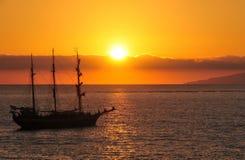 引人入胜的海盗行为船日落 库存照片