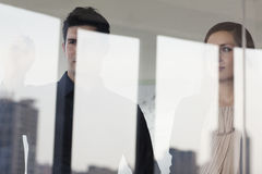 引人注意和看在玻璃墙的另一边的三个商人 库存图片