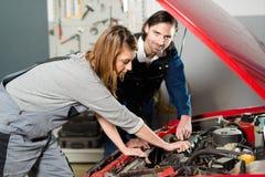 引导一个女性实习生的汽车机械师在车库 免版税库存照片