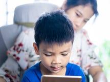 引导她的儿子的母亲使用压片正确 免版税图库摄影
