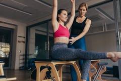 引导正确姿势的教练员一名pilates妇女在健身房 免版税库存照片