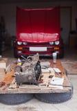 引擎修理,在一辆红色汽车的背景说谎 免版税库存照片