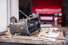引擎修理,在一辆红色汽车的背景说谎 免版税库存图片