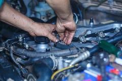 引擎修理,工作在汽车的技工在敞篷下 免版税库存图片
