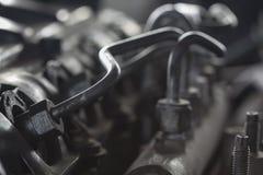 引擎从泵浦的燃料管管到繁多线,车机器设备,修理在车库的机器工作 图库摄影