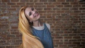 引诱白肤金发的女孩的年轻人使用与头发,观看在照相机,调情的人概念,砖背景 影视素材