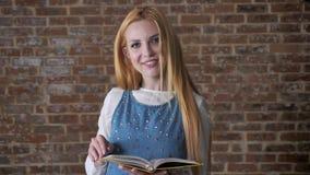 引诱白肤金发的女孩的年轻人是阅读书,观看在照相机,微笑,砖背景 股票视频