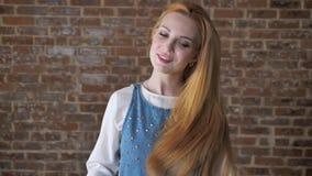 引诱白肤金发的女孩的年轻人观看在照相机,感人的头发,调情的人概念,砖背景 股票录像