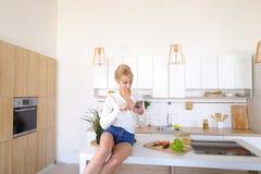 引诱的女孩在互联网上拿着电话并且读信息,坐 免版税图库摄影