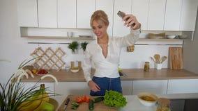 引诱的妇女拿着手机并且叫录影电话,站立在现代烹调桌上  影视素材