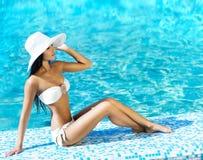 引诱的游泳衣的美丽的女孩在游泳池旁边 库存照片