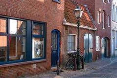 弗利辛恩,荷兰- 2015年4月:一条街道的美丽如画的看法有红砖房子、一老路灯到底和两辆自行车的 免版税库存图片