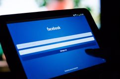 弗罗茨瓦夫,波兰- 2014年4月05日:指向有Facebook的流动app的妇女片剂 库存图片