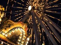 弗累斯大转轮和旋转木马在一个游乐园在晚上打开了与明亮的光 免版税库存图片