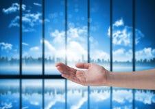 张开有蓝色窗口和城市背景的手 免版税库存照片