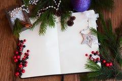 张开笔记本、纸片与圣诞节玩具的,莓果和云杉的枝杈在木背景 免版税库存图片