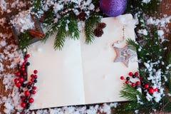 张开笔记本、纸片与圣诞节玩具的,莓果和云杉的枝杈在木背景 库存照片