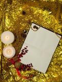 张开笔记本、纸片与圣诞节玩具的,莓果和云杉的枝杈在金背景 免版税库存照片