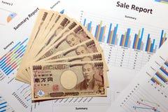10000张日本货币日元钞票和销售报告财政图 免版税库存照片