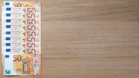 50张欧洲钞票和1欧元硬币在轻的木背景 免版税库存照片
