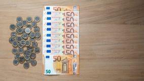 50张欧洲钞票和1欧元硬币在轻的木背景 免版税库存图片