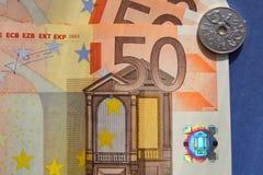 50张欧洲钞票1克罗钠硬币蓝色背景 库存图片