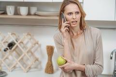 紧张的夫人谈话在电话在厨师屋子里 免版税库存图片