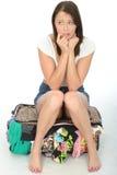 紧张的急切可爱的少妇坐一个溢出的手提箱 免版税库存照片