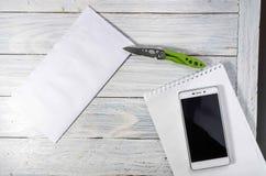 张贴信封、笔记薄和一把刀子在桌面上 免版税库存图片