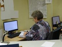 张贴键入邮费邮件办公室操作员秘书妇女运作的类型并且登记登记关于计算机的信息 免版税库存照片