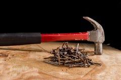 弦槌和钉子在一张木桌上 免版税库存照片