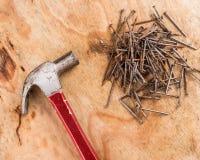 弦槌和钉子在一张木桌上 免版税图库摄影