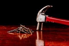 弦槌和钉子在一张木桌上 库存照片