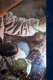 弧焊工工作者在防毒面具焊接金属建筑 免版税库存图片
