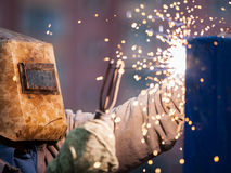 弧焊工工作者在防毒面具焊接金属建筑 免版税图库摄影