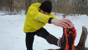 弧被射击舒展腿的黄色外套的有胡子的运动的人在冬天森林里 影视素材