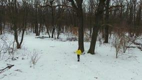 弧被射击跳与跳绳的黄色外套的运动员在冬天森林里 股票录像