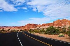 弯曲与陡峭的沙漠岩层的柏油路圆角落在犹他 免版税库存照片