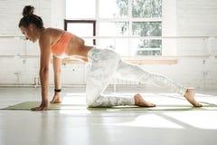 弯曲今后舒展的健身坚强的妇女她的腿坐瑜伽席子 免版税库存照片