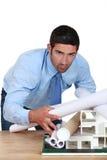 弯曲在书桌的年轻建筑师 免版税库存照片