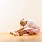 弯曲在她的膝盖的芭蕾舞女演员 库存图片