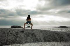 弯曲在岩石的妇女在Bakovern海滩,开普敦的日落 图库摄影
