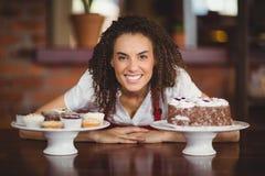 弯曲在巧克力蛋糕和杯形蛋糕的女服务员 免版税库存照片