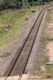弯曲在末端一个平直的金属和具体铁路线的看法的关闭 库存照片