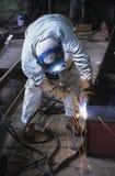 弯曲在焊接下的焊工在工作 免版税库存照片