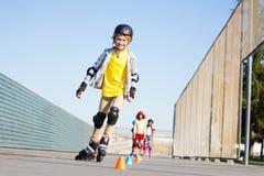弯曲在锥体附近的逗人喜爱的男孩在障碍滑雪路线 免版税库存图片