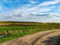 弯曲在绿色领域的土路在蓝色多云天空下 农村的横向 库存照片